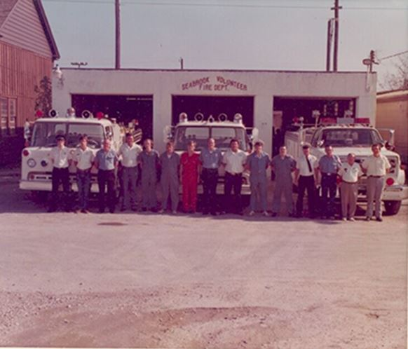 Firemen standing in front of old firehouse